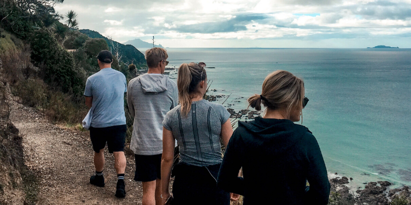 Group of friends walking along The Mangawhai Cliff Walk overlooking the ocean below