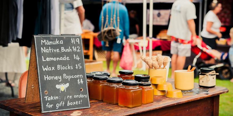Various types of honey for sale at a stall set up at The Mangawhai Village Market
